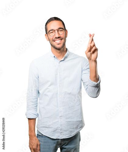 Happy young man doing a crossed fingers gesture Fototapeta
