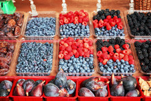 Fresh Blueberries, Raspberries, Blackberries, Figs And Dry Plums Displayed In Plastic Containers On An Outdoor Market Stall