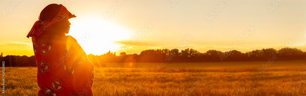 Fototapeta African woman in traditional clothes in field of crops at sunset or sunrise panorama