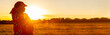 canvas print picture - African woman in traditional clothes in field of crops at sunset or sunrise panorama