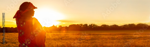 African woman in traditional clothes in field of crops at sunset or sunrise panorama