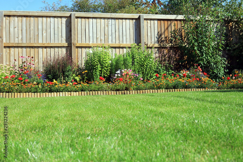Obraz Shrubs And Flowers In A Border With A Grass lawn Surrounded By A Wooden Fence. - fototapety do salonu