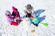 Leinwandbild Motiv Happy couple with two children making big snowman