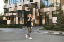 Portrait Of A Fashionable Man In A Black Shirt And Gray Pants Walking Down The Street With Business Papers In His Hands And Drinking Coffee. Full Length Photo Of Stylish Man Walking Down The Street