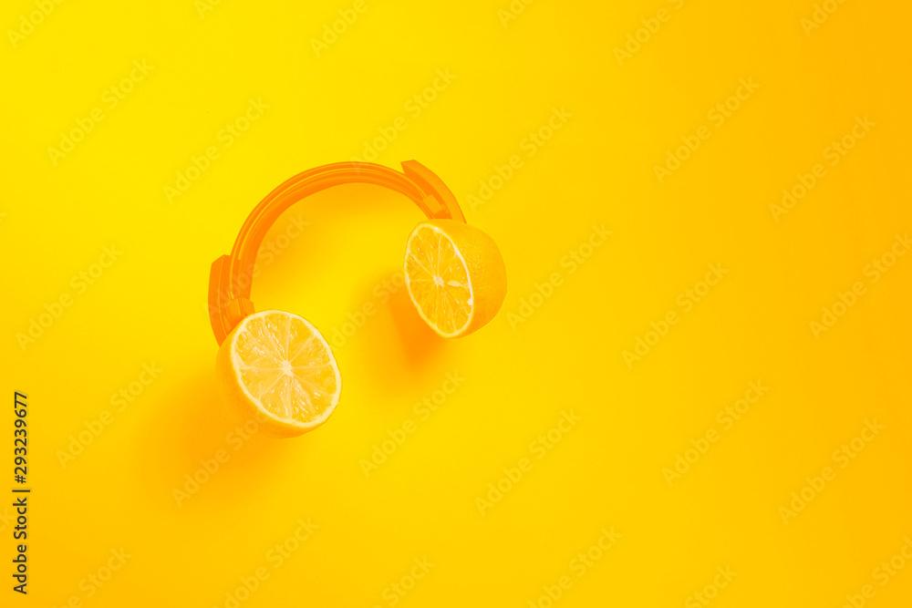 Yellow citrus headphones. Creative concept for summer parties.