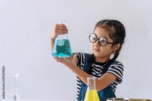 Stampa su Tela Little 6s cute girl with microscope holding laboratory bottle with water experiment study scientists at school