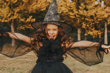 Cute Girl In Costume Of Witch On Nature Background