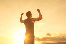 Strong Confident Man Flexing His Arms Facing The Sunset.