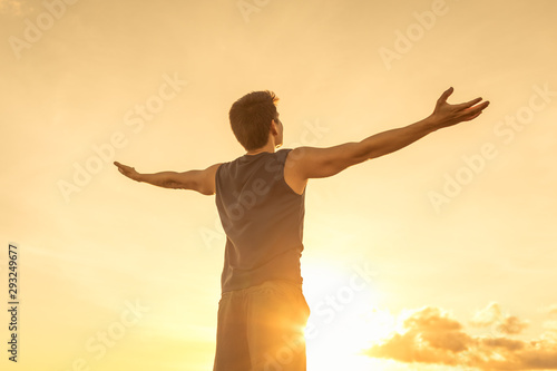 Obraz Success achievement accomplishment and motivation concept with man sunset silhouette celebrating arms up raised outstretched outdoors in nature  - fototapety do salonu