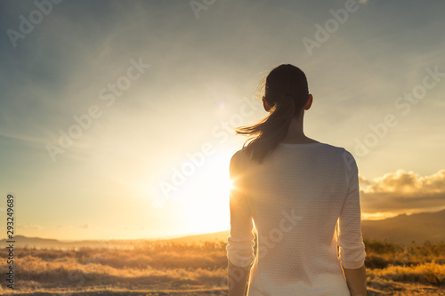 Life is beautiful. Woman standing facing a beautiful golden sunrise.