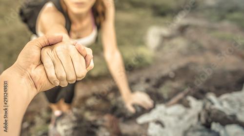 Fototapeta Male hiker giving his hand helping friend climb up a mountain.  obraz