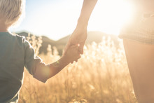 Mother Little Child Holding Hands Walking In A Grass Field At Sunset.