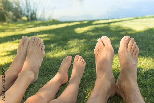 Deurstickers Ontspanning Happy family of three relaxing feet in the grass lake side.