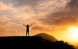 Success achievement accomplishment and motivation concept with man sunset silhouette celebrating arms up raised outstretched trekking climbing outdoors in nature