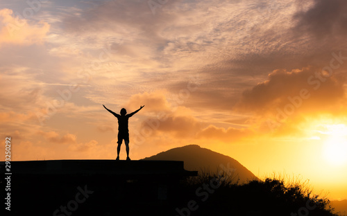 Obraz Success achievement accomplishment and motivation concept with man sunset silhouette celebrating arms up raised outstretched trekking climbing outdoors in nature  - fototapety do salonu
