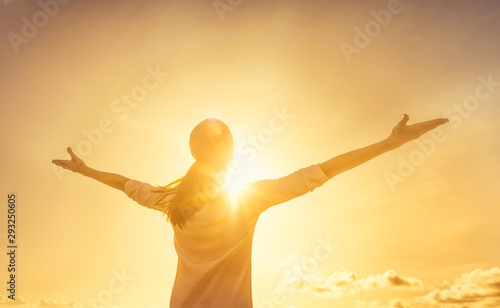 Obraz Carefree woman outdoors with arms outstretched feeling happy and free.  - fototapety do salonu