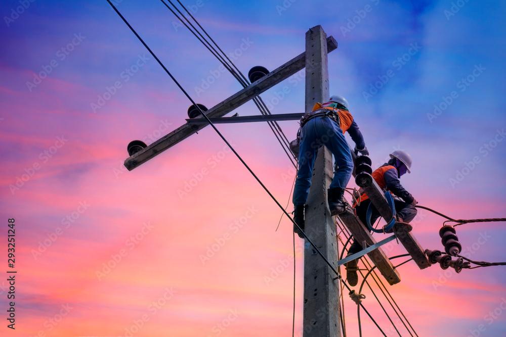 Fototapeta Electrician lineman repairman worker at climbing work on electric post power pole