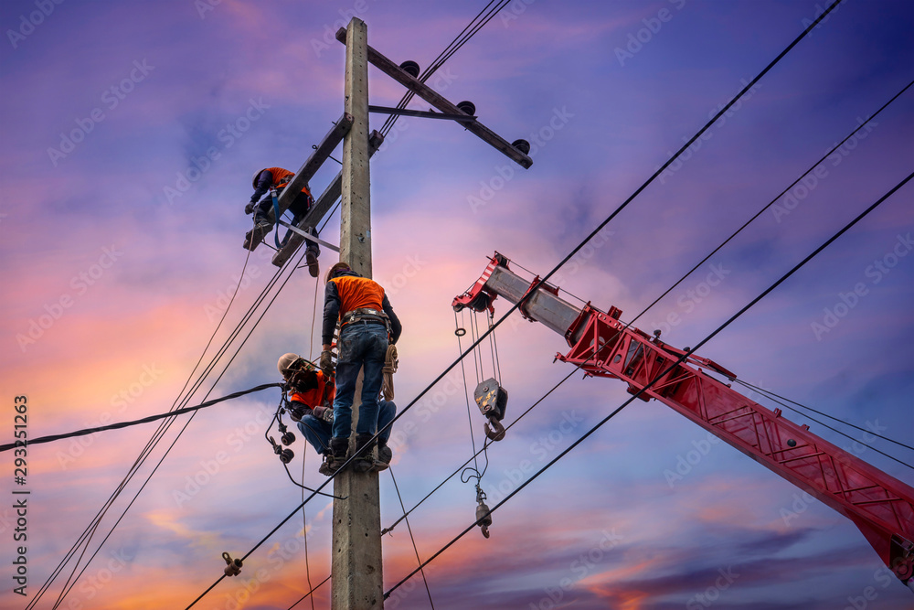 Fototapeta Electrician lineman with cranes and hoists repairman worker at climbing work on electric post power pole