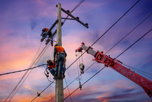 Electrician Lineman With Cranes And Hoists Repairman Worker At Climbing Work On Electric Post Power Pole
