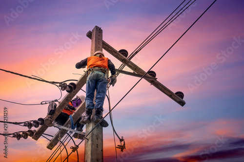Fotomural  Electrician lineman repairman worker at climbing work on electric post power pol