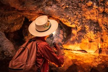 Horizontal Shot Of A Female With A Hat Walking With A Flashlight In The Cave