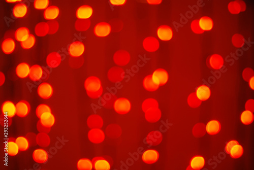 Fototapeta Red-orange trendy festive background of blurry Christmas lights