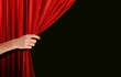 canvas print picture - Hand opening red curtain over black background