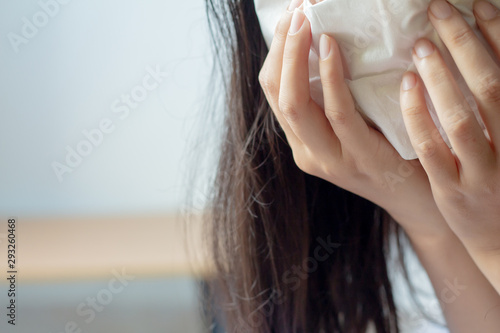 Fotografie, Tablou  Close up sick young woman has runny nose, blowing her nose into paper