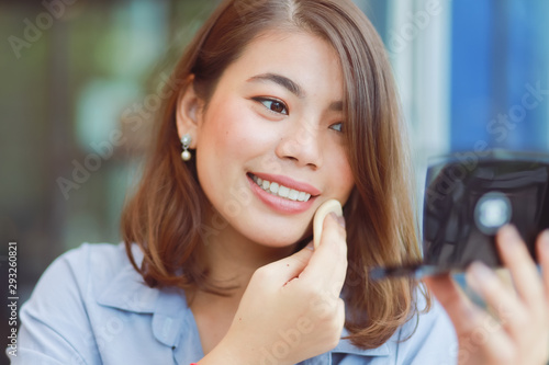 Photo Asian woman make up her face with lipstick in cafe