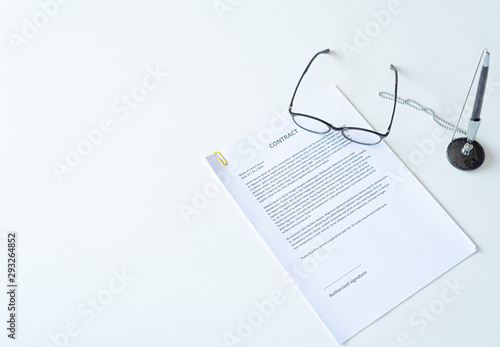 Fotografía  White table with paper contract detail and empty space to sign authorized signat