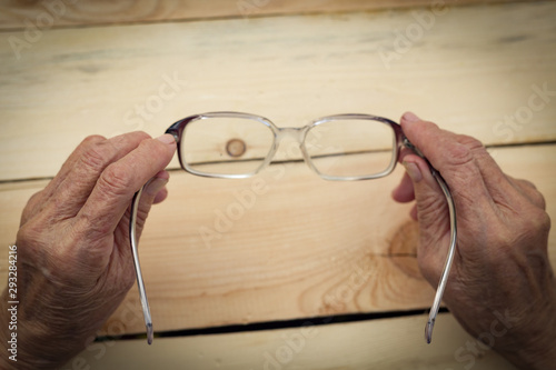 Hands of an elderly man hold glasses Canvas Print