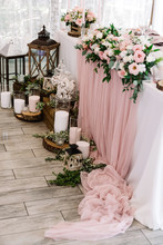 Beautiful Flowers On The Wedding Table And Candles In Large Glass Flasks On Wooden Stands Near It.
