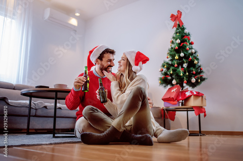 Foto Happy handsome caucasian couple with santa hats on heads sitting on the floor with beer bottle in hands and cuddling