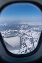 View Of Beautiful City Covered By Snow From A Airplane Window.