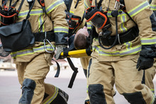 Professional Firefighter Firefighters Fireproof Suits, White Helmets And Gas Masks Carry The Injured Person On Stretchers