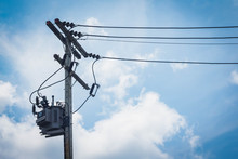 Electric Tranformer On The Eletric Cement-pole. White Clouds And Blue Sky