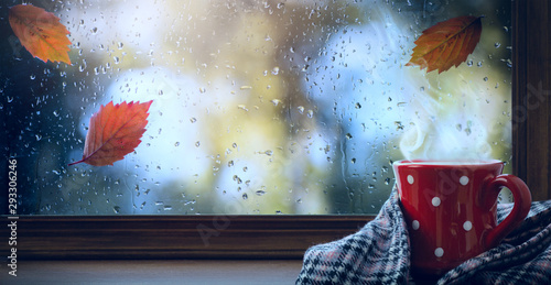 Canvas Print red cup with hot drink and wet autumnal window; Autumn season background