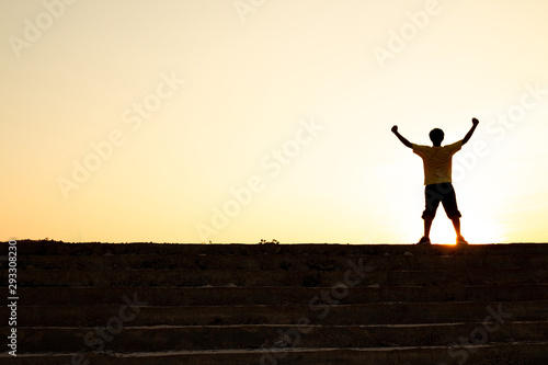 The young man on top of the stairs going to the sunset sky, Ambitions concept and Successful Wallpaper Mural