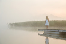 Young Woman In White Dress Standing Alone On Footbridge And Staring At Lake. Mist Over Water. Foggy Air. Chilly Morning. Empty Place For Sentimental, Inspirational Text, Quote Or Sayings. Back View.