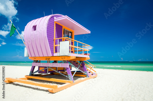 Fotomural Vibrant sunny view of lifeguard tower painted pastel colors under bright blue sk