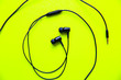 canvas print picture - Earphones lying on the green background. Modern music concept. Audio technology.