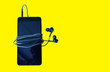 canvas print picture - Black smartphone with earphones isolated on yellow background. Modern technology connection. Digital cell.