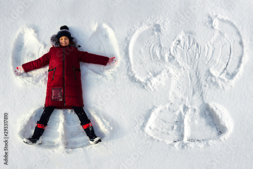 Fotomural  The girl lies in the snow and makes a snow angel