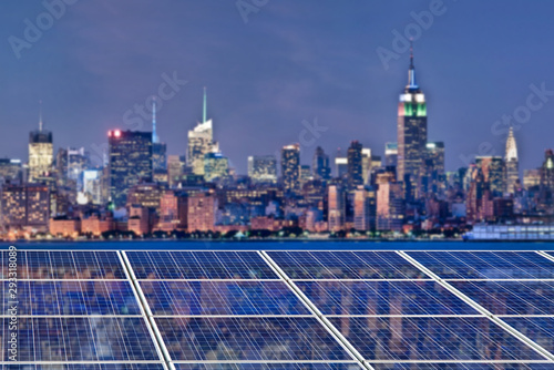 Fototapeta Blue solar cell panels, New York skyline illuminated at night in the background obraz