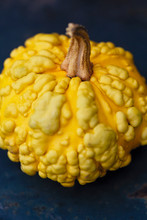 Close-up Of A Yellow Gourd On A Dark Surface