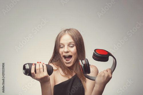 Joyable attractive fashion pretty girl listening music with headphones, speaker, record player, holding thm in hands and wearing red gloves, take pleasure with song. Lifestyle woman concept - 293331406