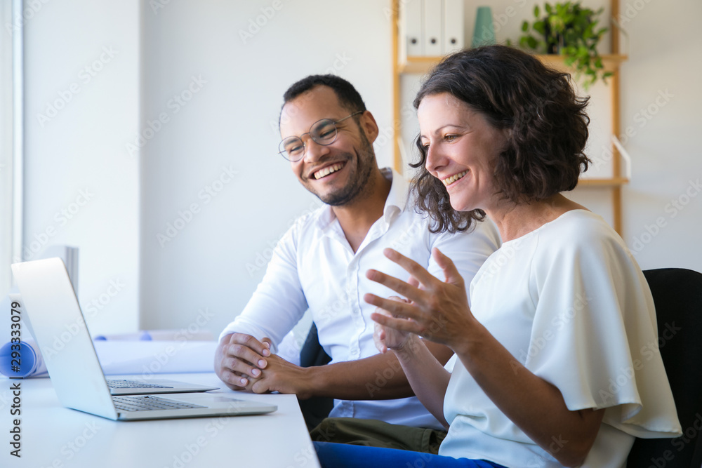 Fototapeta Cheerful colleagues using laptop for video call. Man and woman sitting at workplace together, looking at monitor and laughing. Communication concept