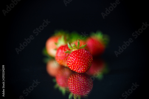 ripe red strawberries on a black background - 293334299