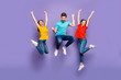 Full length size body photo of three funny funky ecstatic excited delightful buddies having fun on weekend isolated violet background