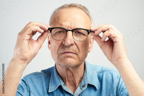 Photo Old man in eye glasses with diopters squints, stares intently at the camera isolated on a white background